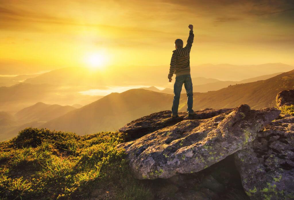 頂上で拳を上げる男性