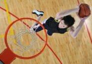体育館でバスケットボールをプレーする男性