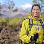 春山をハイキングする男性