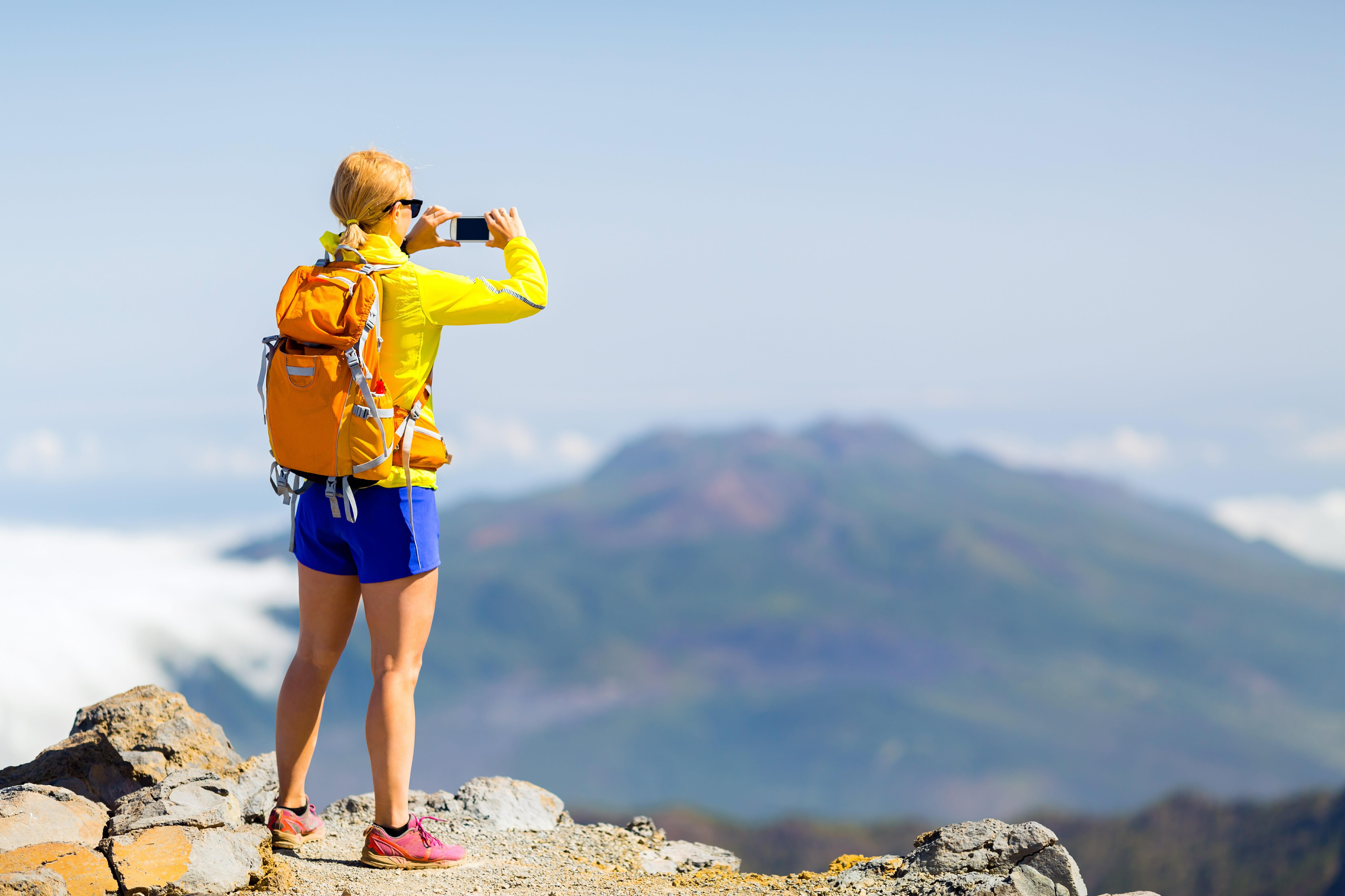 山で写真をとる女性