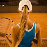 屋外でテニスをプレーする女性
