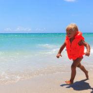 ライフジャケットを着てビーチを歩く女の子