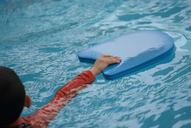 プールで泳ぐ練習をする男の子