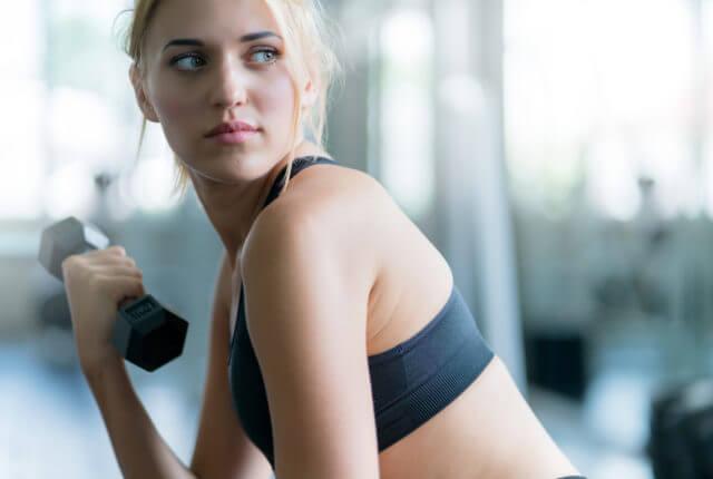ジムでダンベルを使いトレーニングする女性