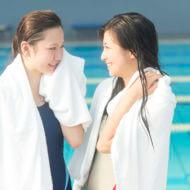プールから上がってタオルをかけている女性