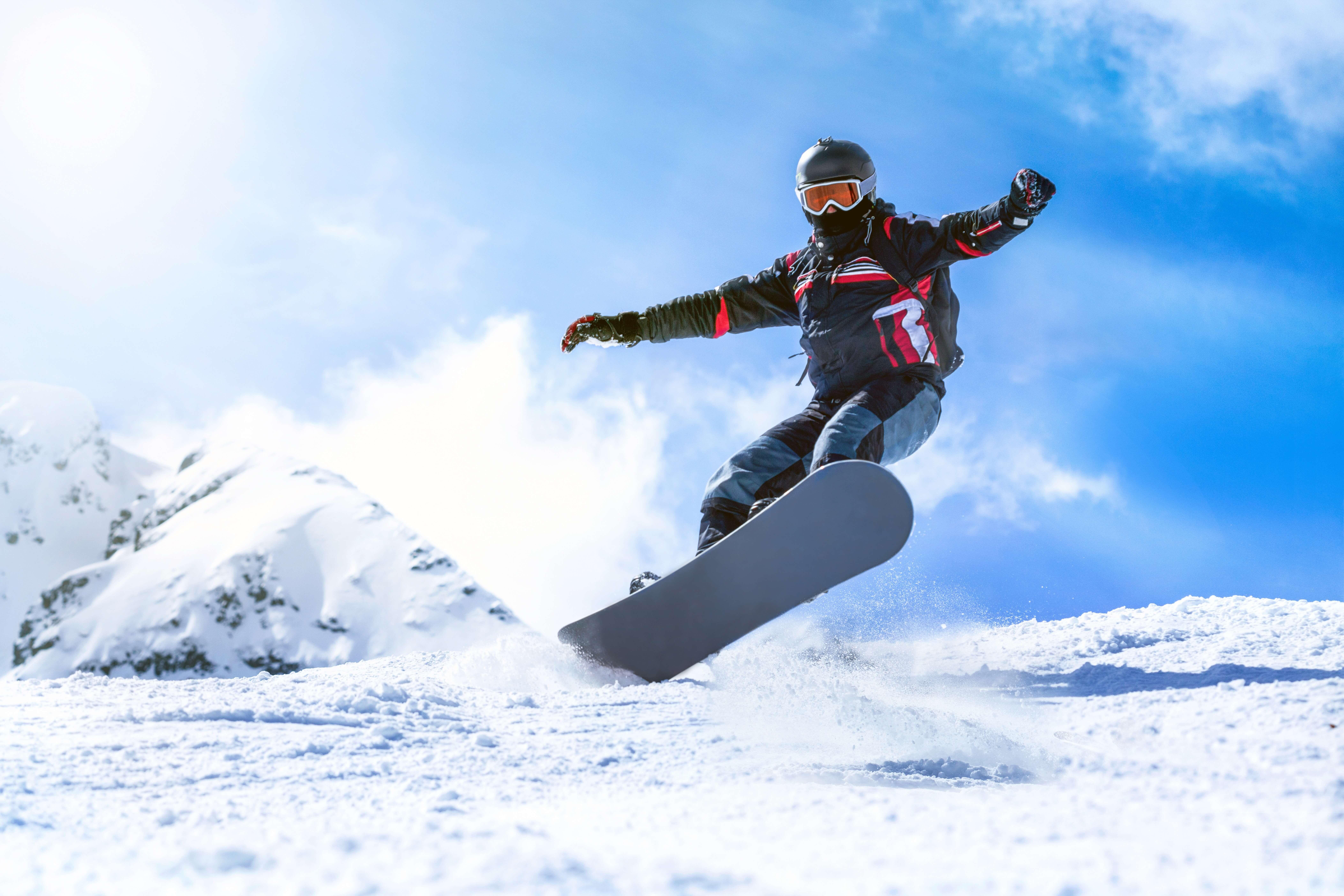 スノーボードで滑走する男性