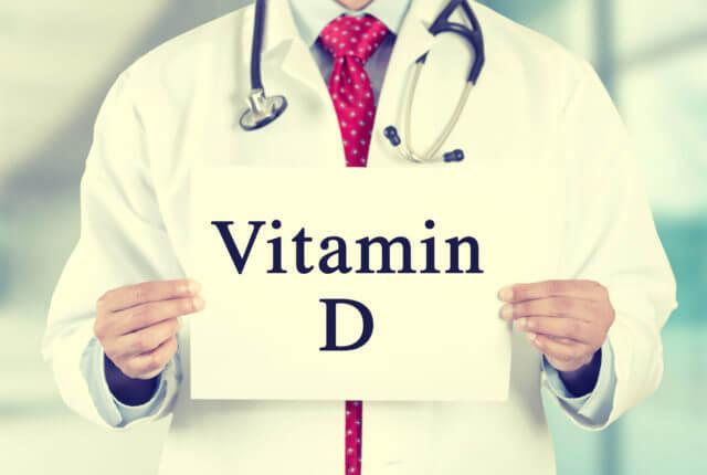 ビタミンDの札を掲げる医師