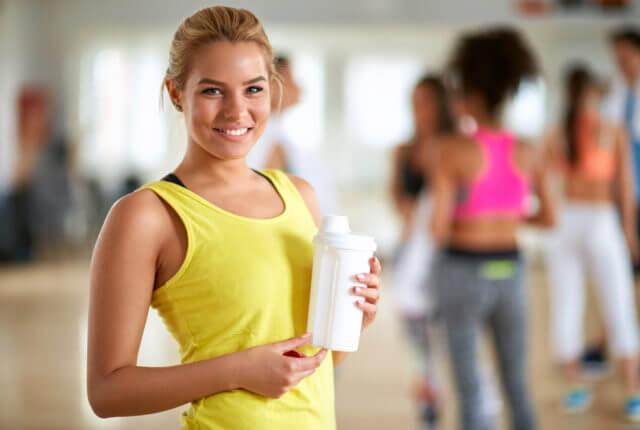 ジムでトレーニング後にプロテインを準備する金髪の若い女性の写真