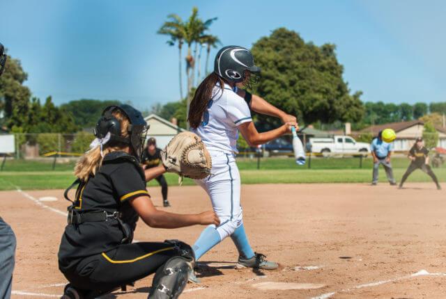 ソフトボールでスウィングする女性プレーヤー