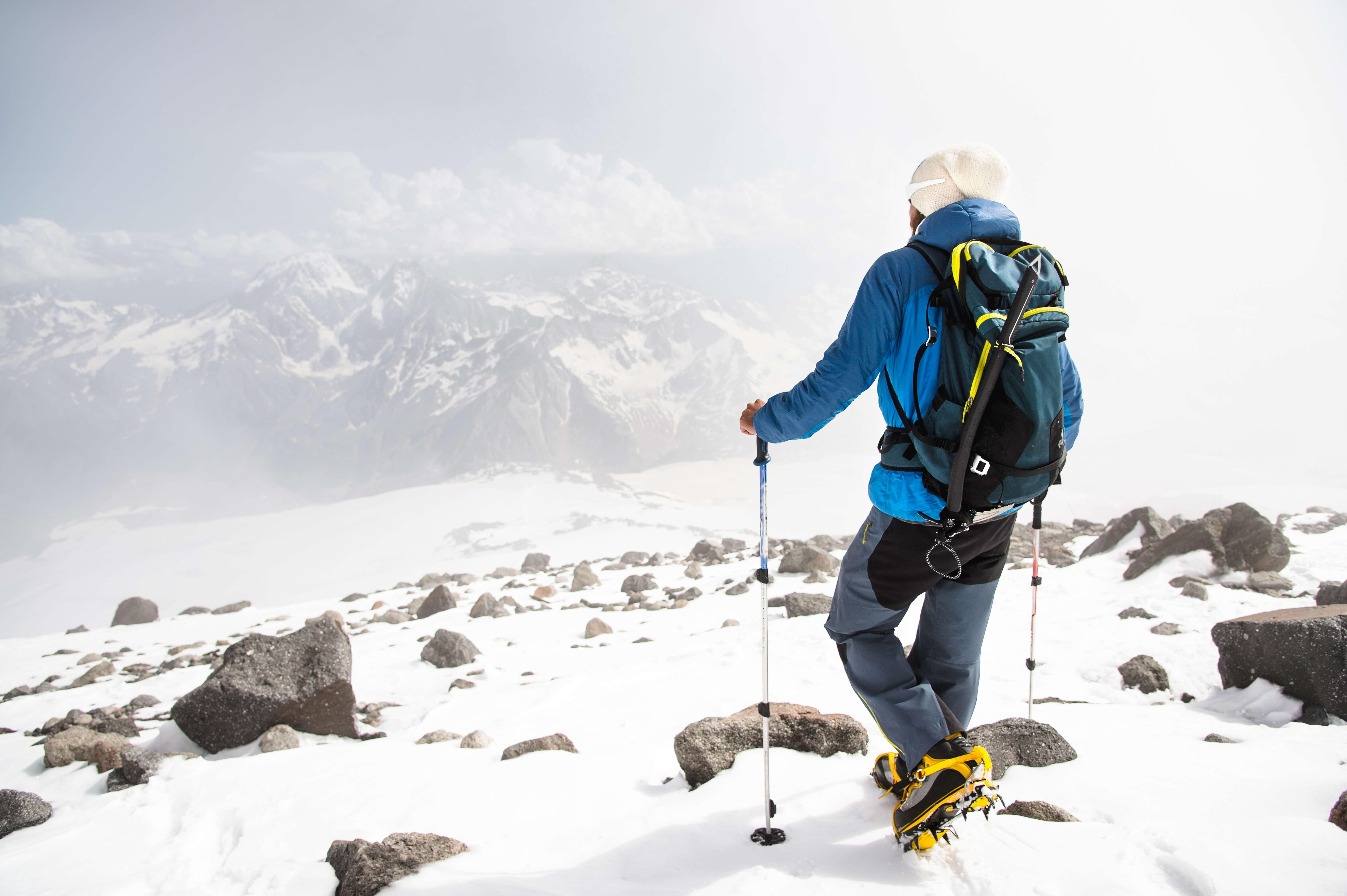 雪山でピッケルを持つ男性