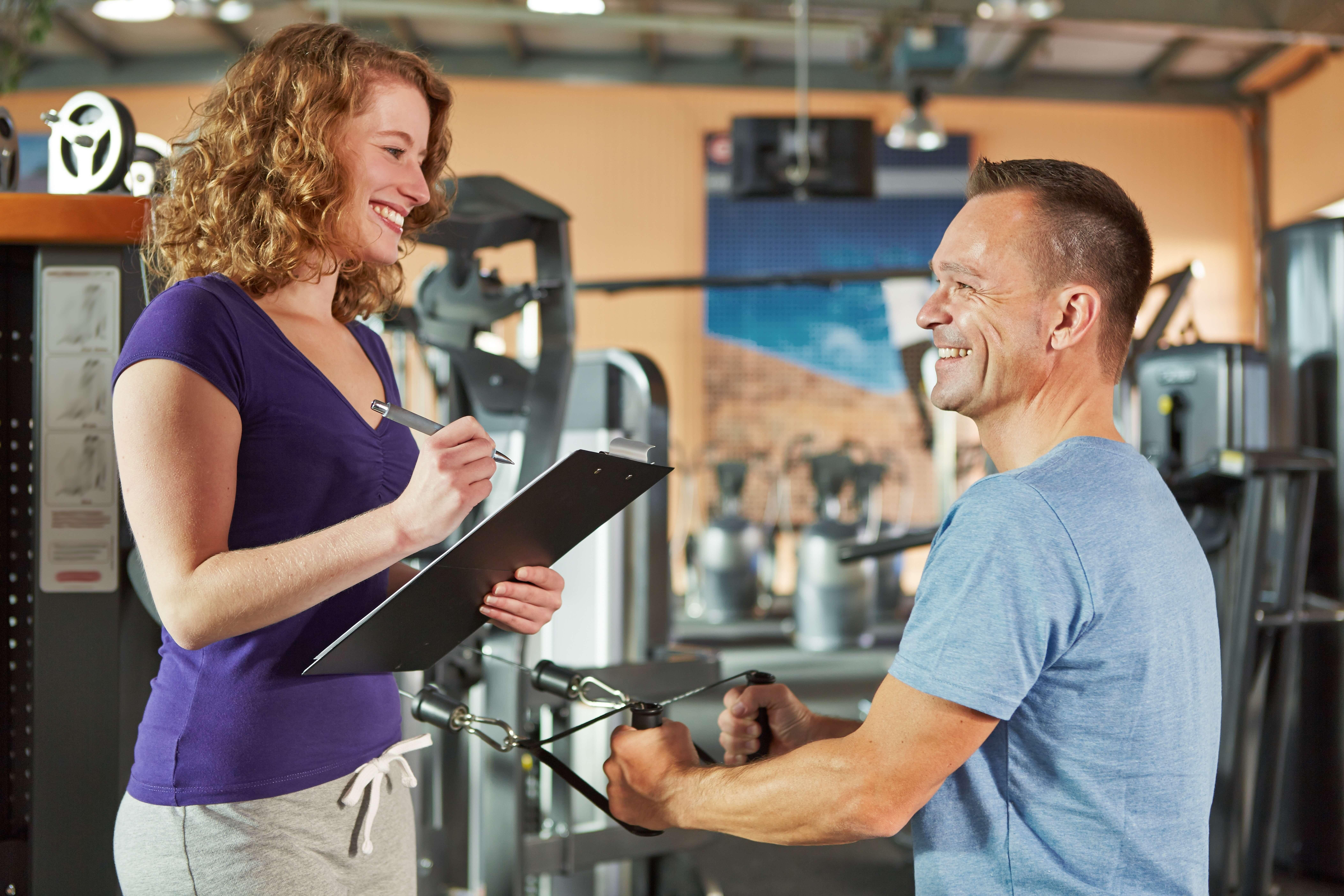 女性トレーナーとトレーニングする男性