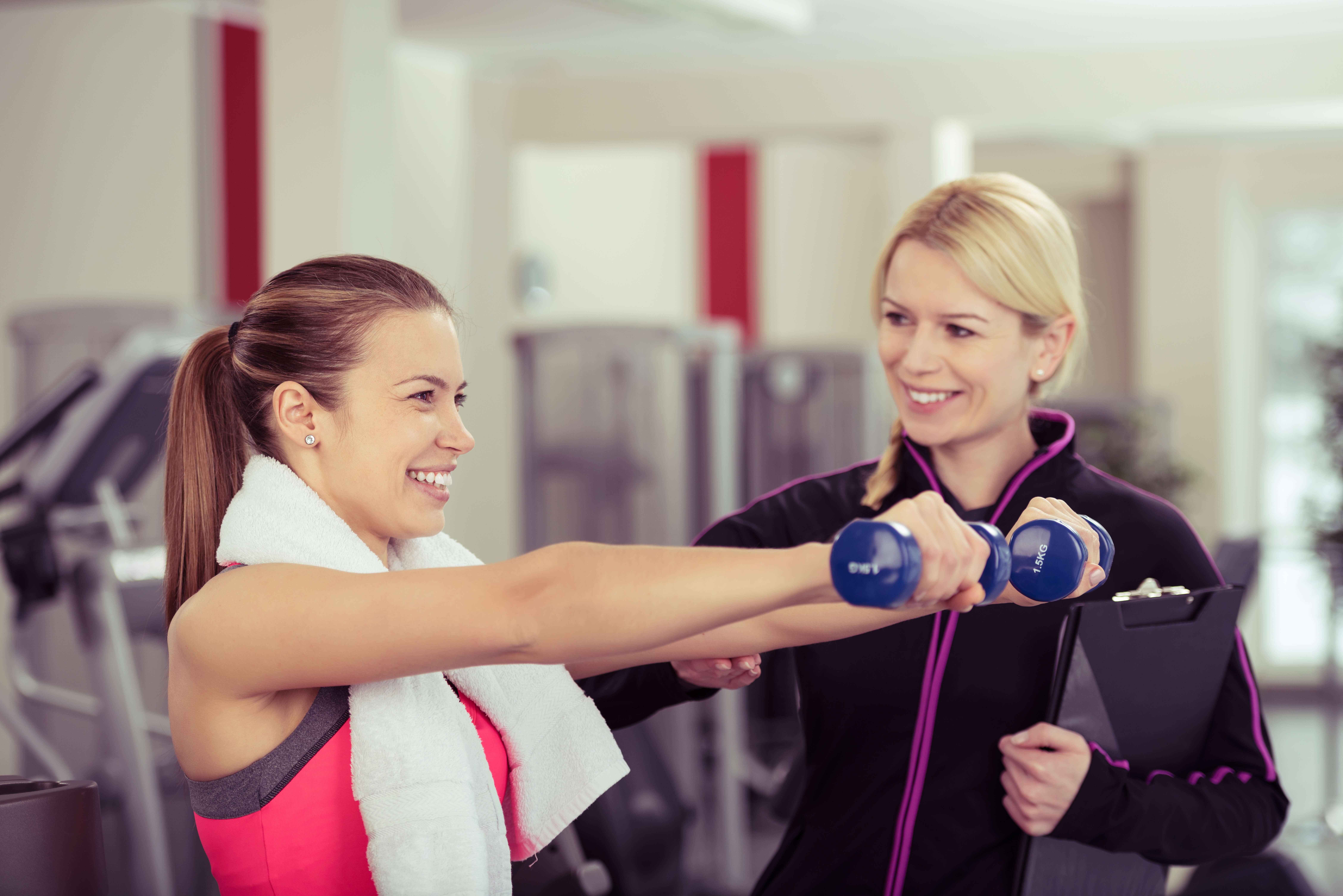 パーソナルトレーナーが彼女の進歩を監督しながら手の重量を使用して笑顔の女性