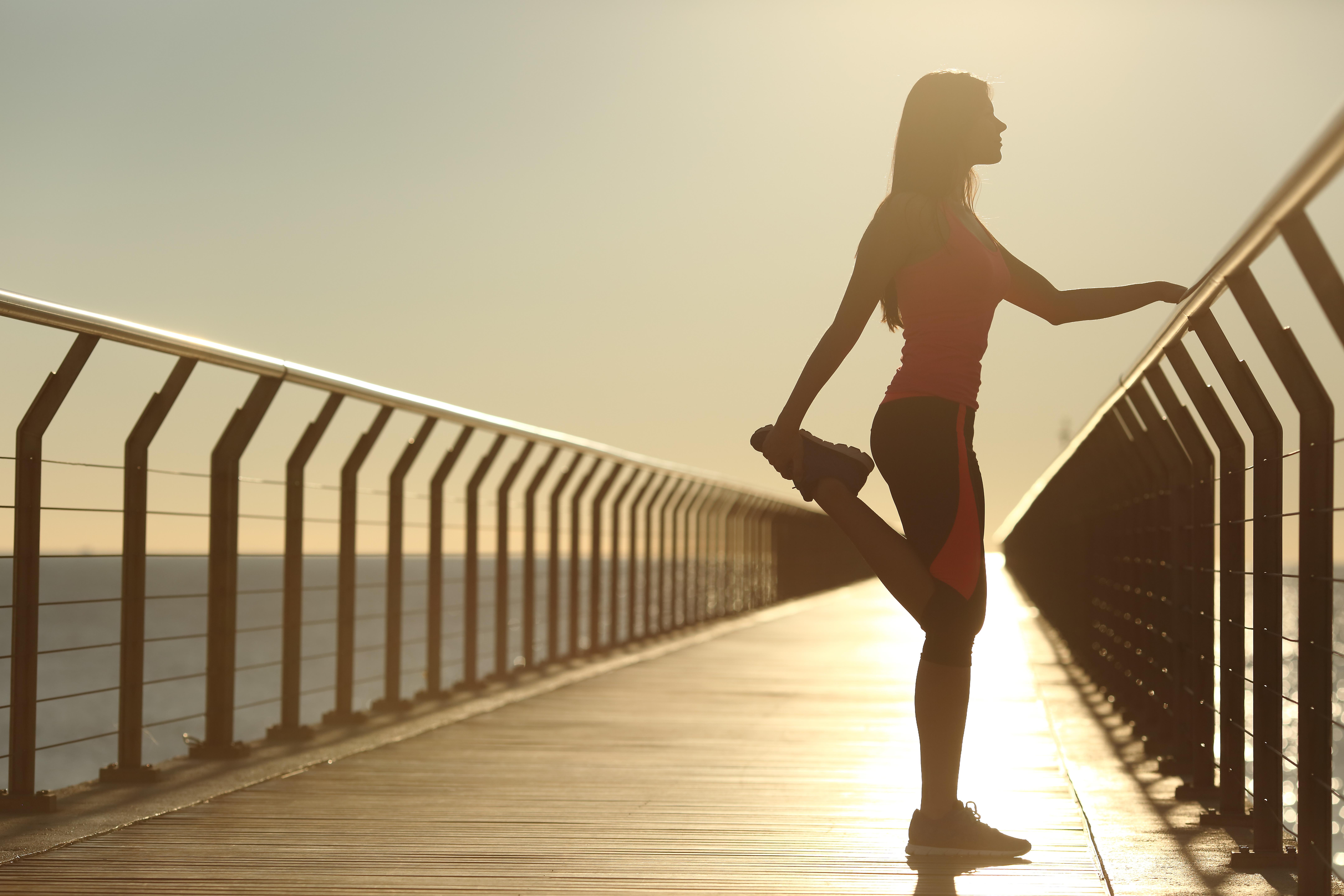 日没で実行した後橋の上ストレッチ運動女性のシルエット