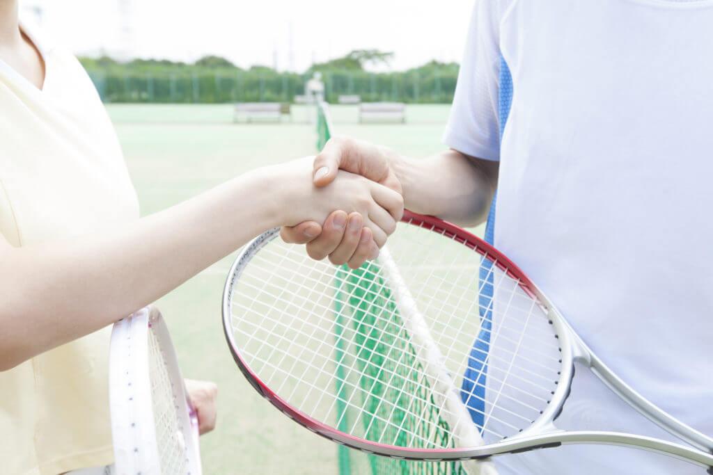 テニスコートで握手する二人