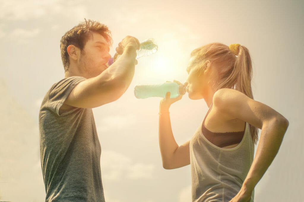 トレーニン後に水分補給する男女