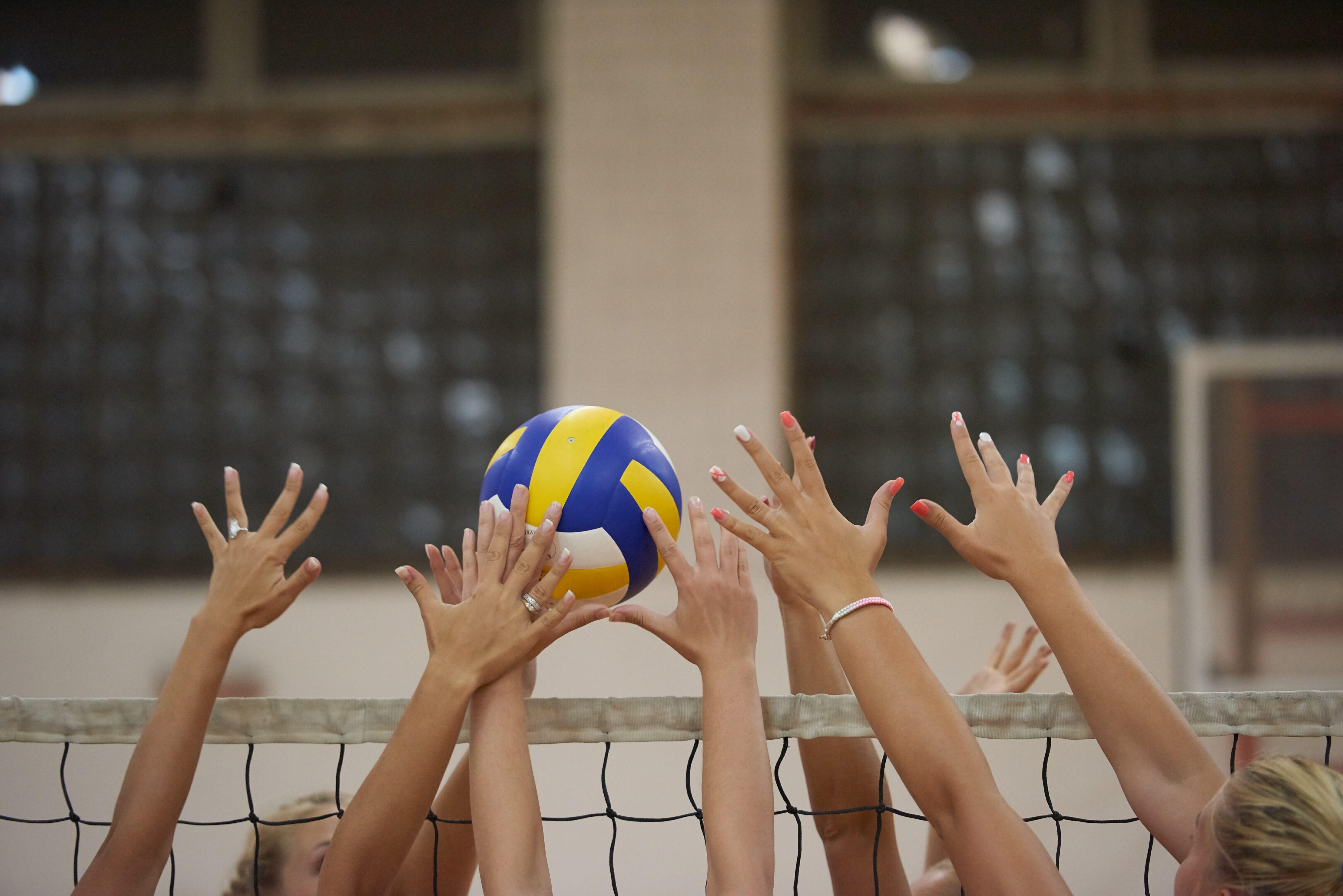 ネット上でプレイするバレーボール選手たち