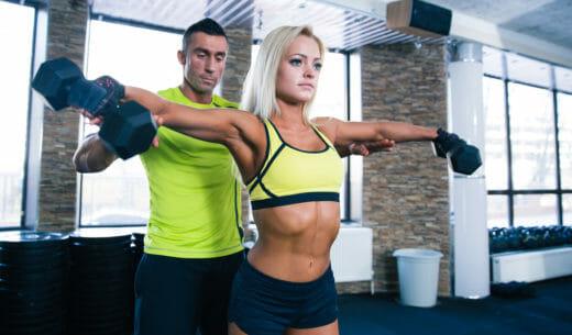 ダンベルを持ち上げる女性とトレーナー