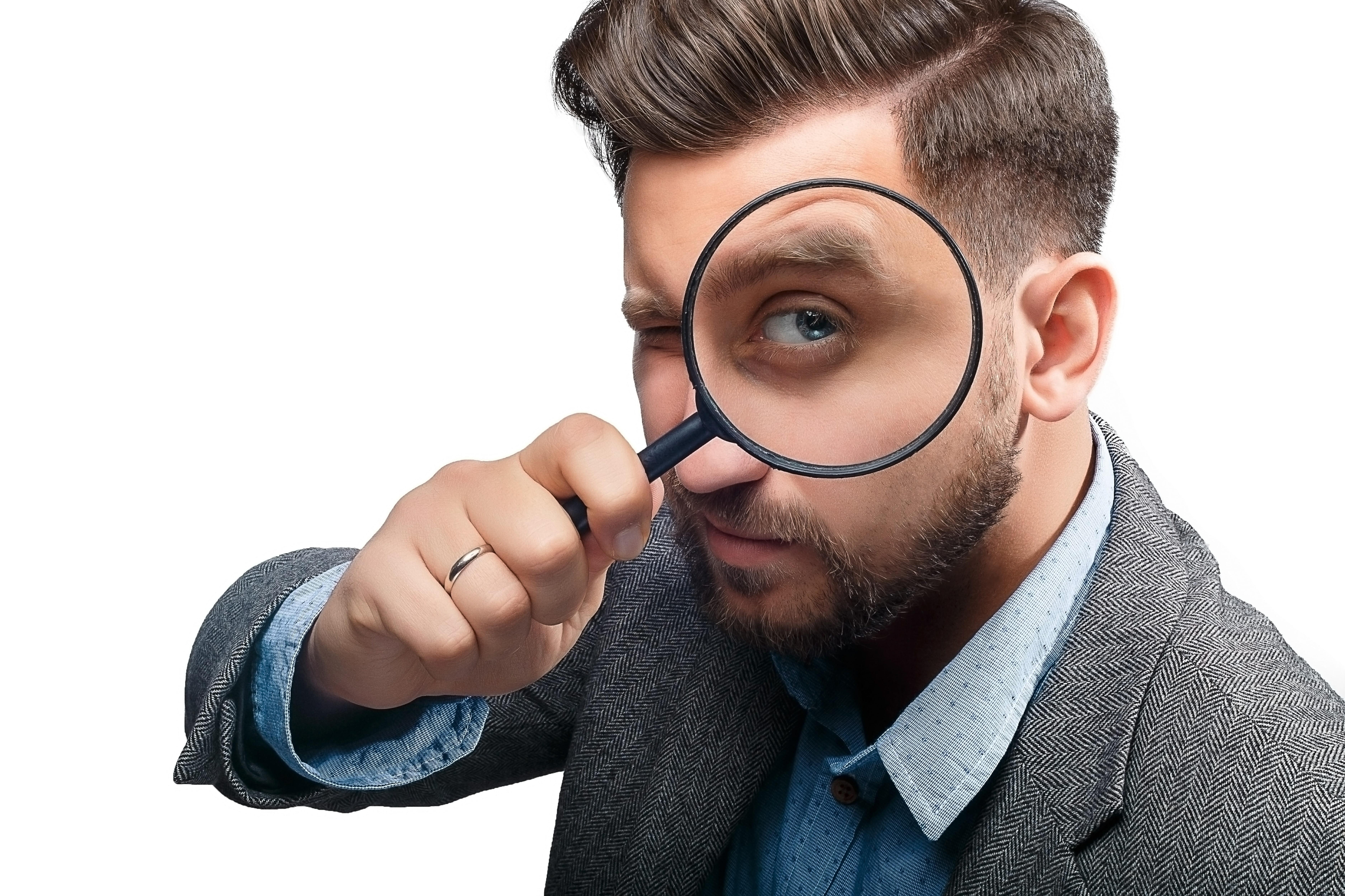 虫眼鏡で覗く男性