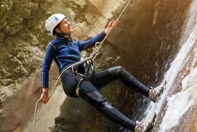 絶壁をロープ伝いで登る登山者
