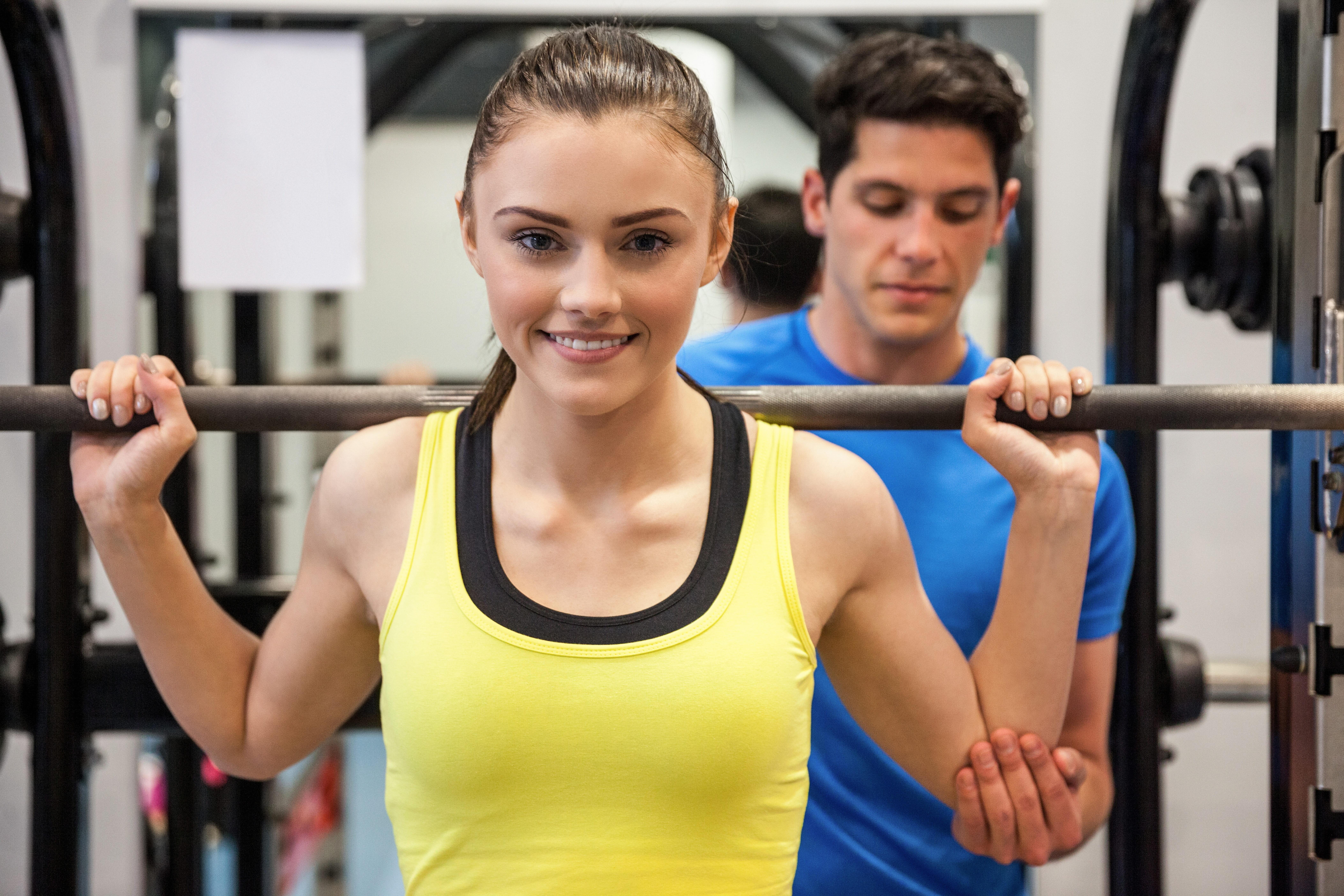 バーベルを持ち上げる女性とトレーナー