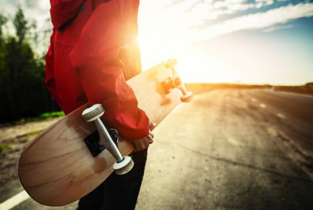 スケートボードを抱えてたつ人