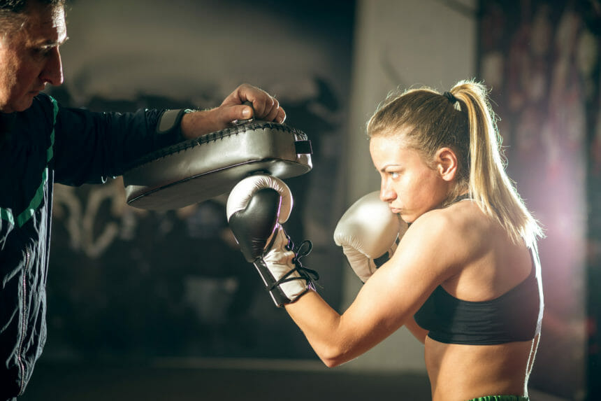 キックボクシングのスパーリングを受ける女性