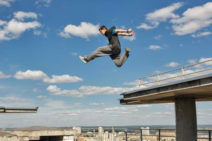 屋根をジャンプするパルクール選手