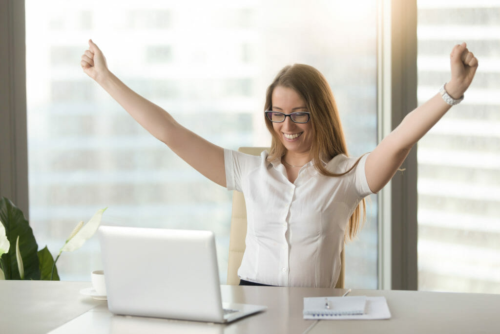 仕事での成功に手を上げて喜んでいる女性