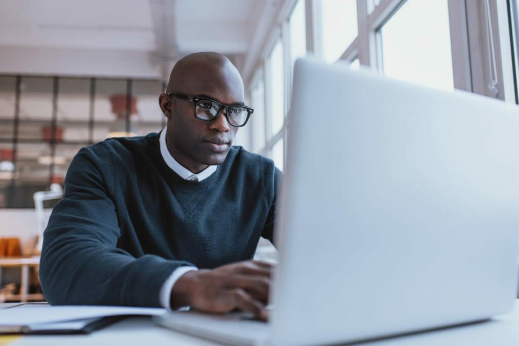 若いビジネスマンがオフィスでラップトップPCを使い働いている