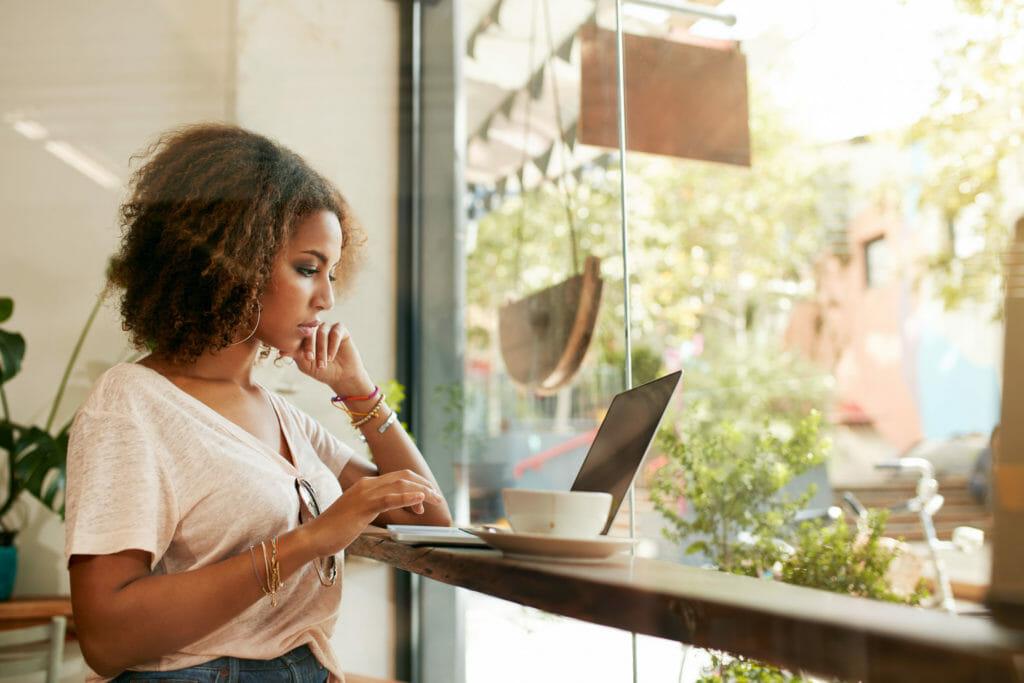 カフェでラップトップPCを操作する女性